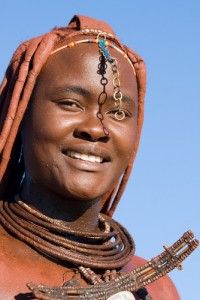 A Himba woman wearing traditional jewellery. The Himba rub red ochre over their bodies, giving them a distinct red colour to their hair and skin.