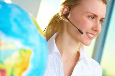 Travel agent with headset consulting client