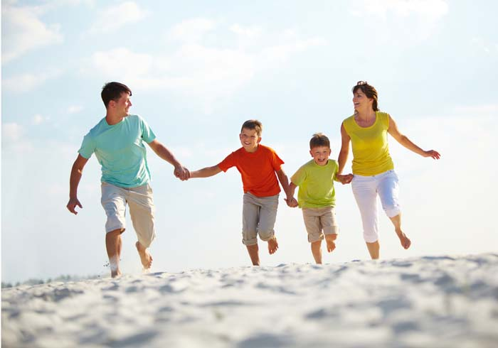 happy family running down the beach on summer