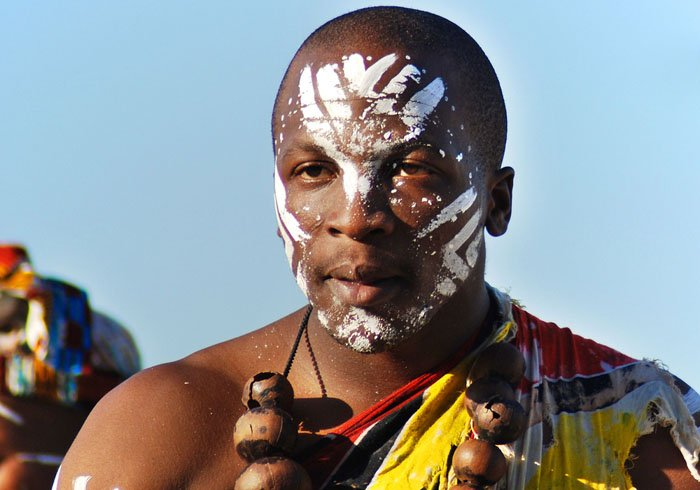 Young man wears traditional clothing during presentation of a Zulu show