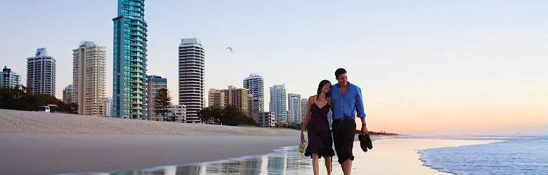 Couple Walking at Sunset Along Surfers Paradise Beach, Gold Coast, Queensland, Australia