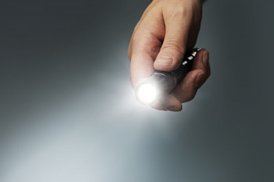 Man's Hand Holding a Small LED Flashlight_131821802
