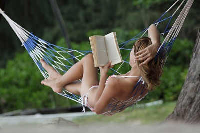 Young Woman Reading a Book Lying in Hammock on Beach_132610445