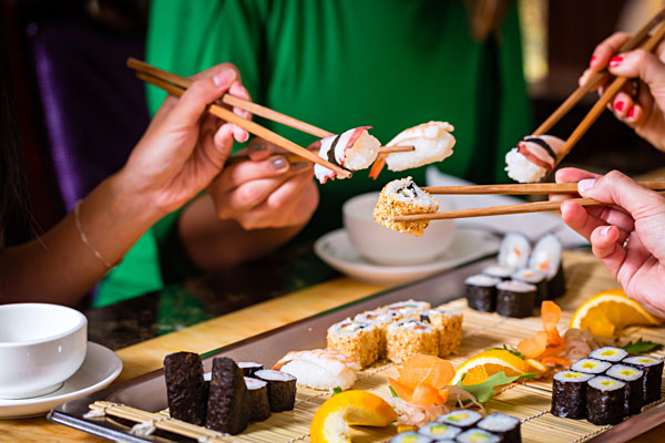 Young people Eating Sushi in Asian Restaurant_216328840