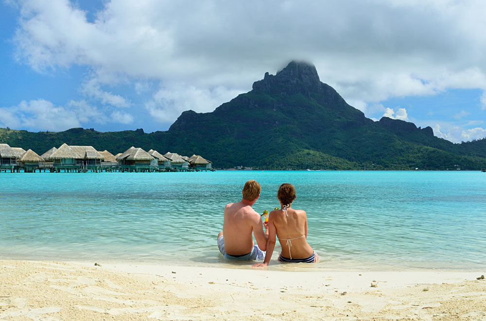 A Couple Drinking a Cocktail on the Beach of a Luxury Vacation Resort With View of Bora Bora, Tahiti