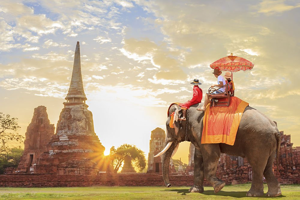 Tourists on Elephant tour in Ayutthaya at Sunrise, Thailand