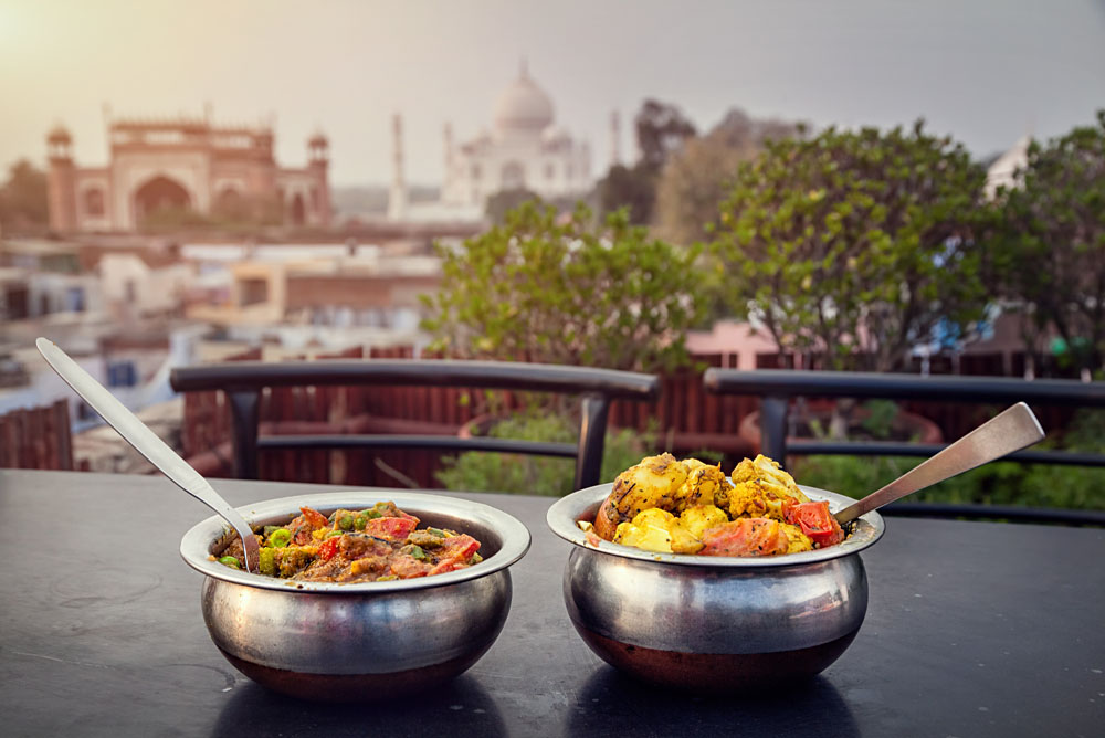 Traditional Indian food in Metal Dish on Rooftop Restaurant with Taj Mahal Background, Agra, Uttar Pradesh, India
