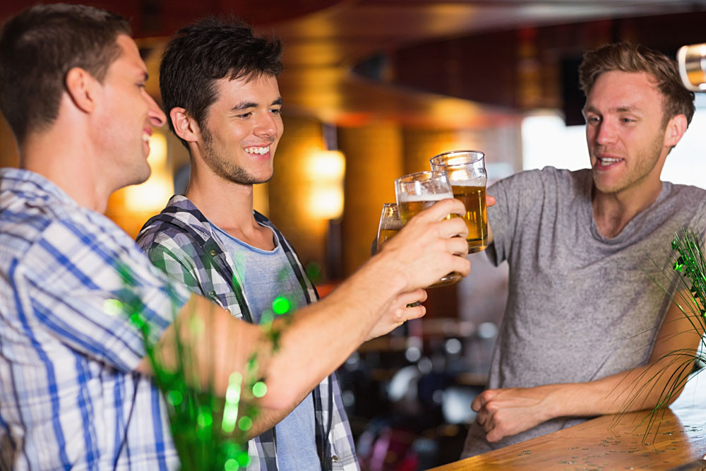 Happy Male Friends Toasting with Beer on St Patricks Day in a Bar