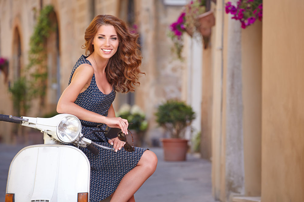 Young Beautiful Italian Woman Sitting on an Italian Scooter, Italy