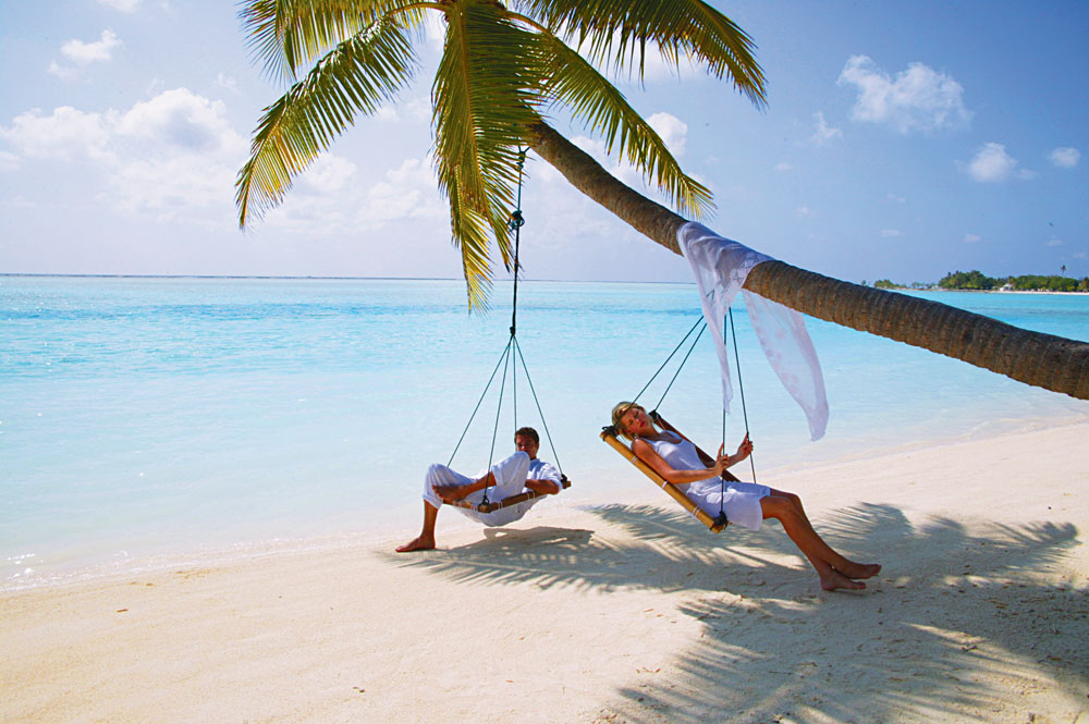 Couple Relaxing on a Tree Swing in the Maldives