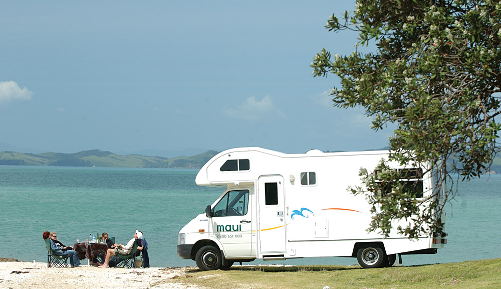 Friends Relaxing Near Their Maui Motorhome in New Zealand