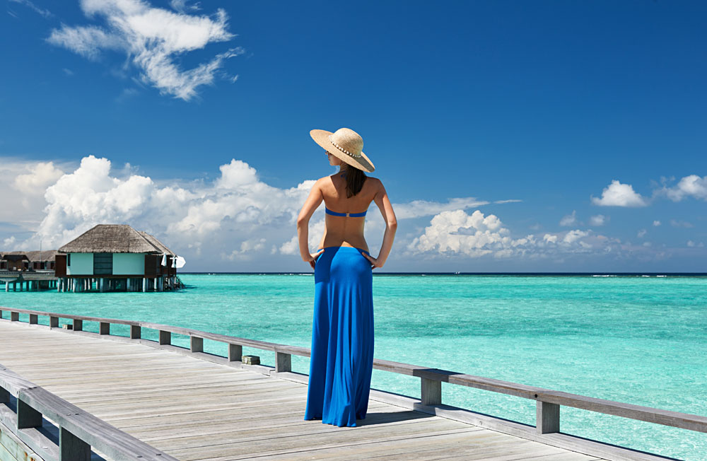 Woman on a Tropical Beach Jetty in the Maldives