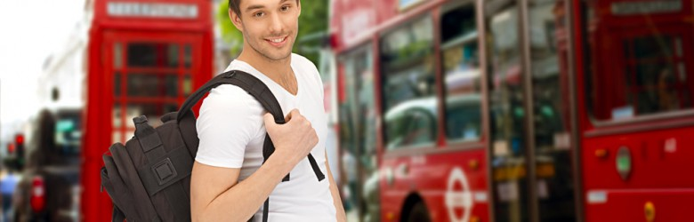 Young Man with Backpack and Book in Front of Double Decker Bus and Phone Booth, London, England, UK