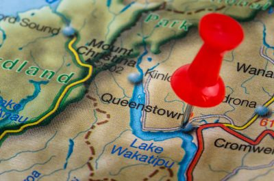 Close Up of a Map of New Zealand with a Red Pushpin Highlighting Queenstown