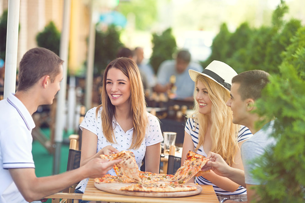 Four Cheerful Young Friends Sharing Pizza in an Outdoor Cafe