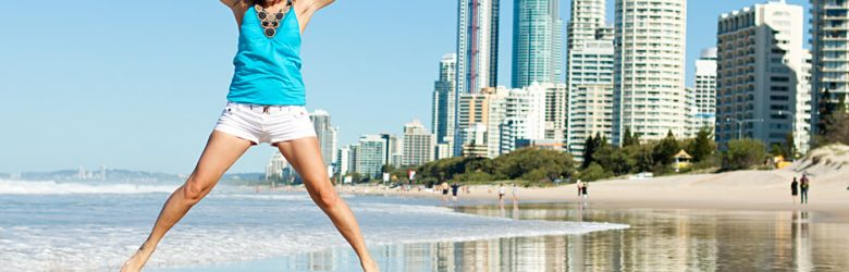 Happy Woman Jumping for Joy on Beach Along the Gold Coast, Queensland, Australia