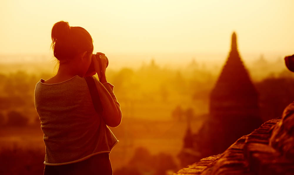 A female traveler photographing temples at Bagan Myanmar Asia at sunrise as part of a group tour.