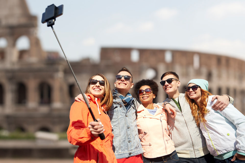 Group travel and sharing a photo at the Coliseum in Rome