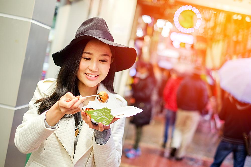 Young Asian Woman Eating Dumpling Batter (Takoyaki) on Street in Hong Kong