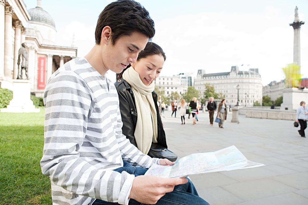 Japanese Tourist Couple Reading Map at Trafalgar Square in London, England, UK