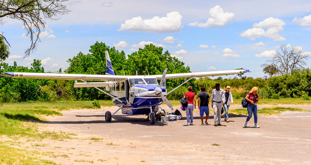 Tourists on an African safari arrive by small plane to the Okavango River Delta National Park in Botswana