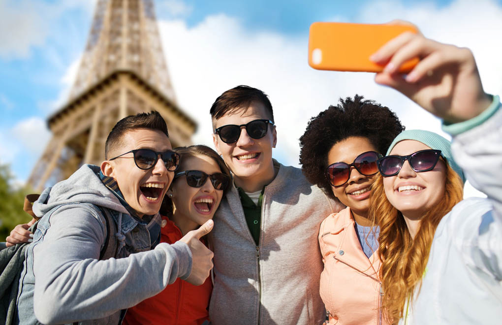 A group of friends taking a selfie in front of the Eiffel Tower in Paris
