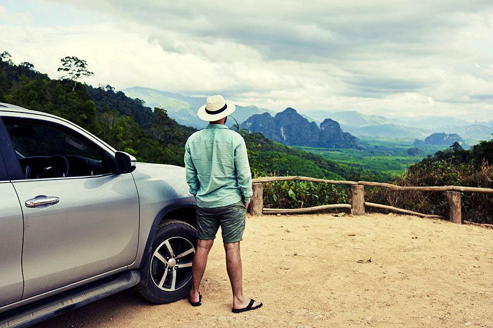 Male Traveller with SUV Admiring Landscape in Thailand
