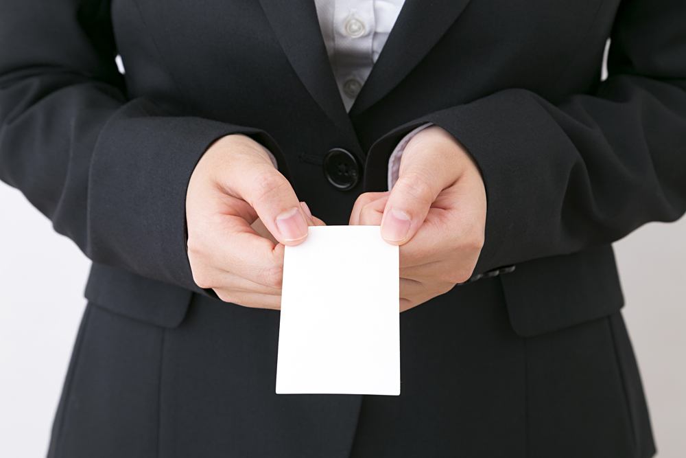 Business Woman Handing Over a Business Card with Both Hands, Japan