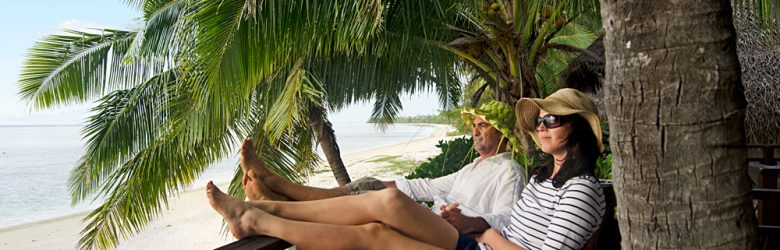 Couple Relaxing on Veranda of Beach Villa, Aitutaki lagoon, Cook Islands