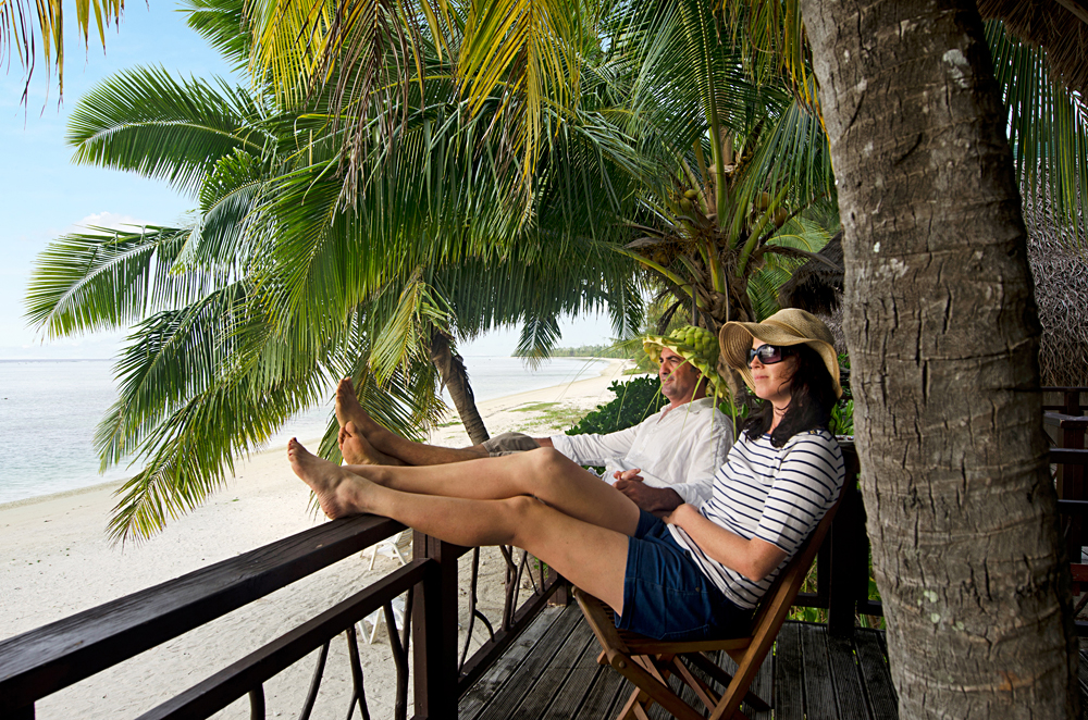 Couple Relaxing on Veranda of Beach Villa, Aitutaki lagoon, Cook Islands