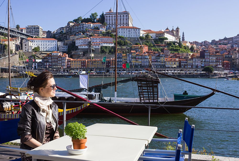 Young Woman Sitting in a Cafe on the Banks of the River Douru, Porto, Portugal