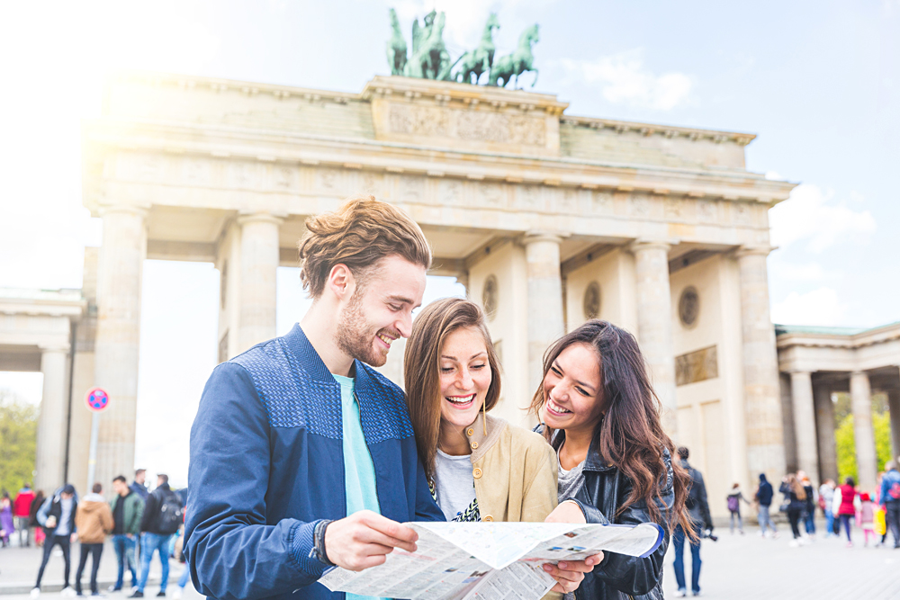 Friends looking at a map with Brandenburg Gate in background, Berlin, Germany