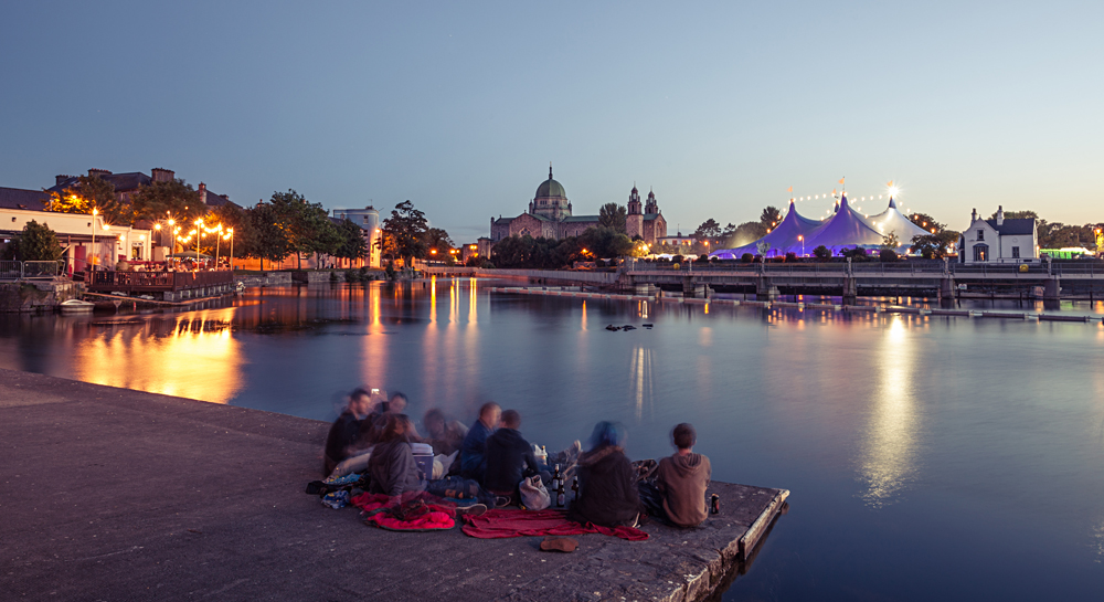 Enjoying the evening during Galway Art Festival with Big Top and Cathedral on the bank of Corrib river in Galway, Ireland