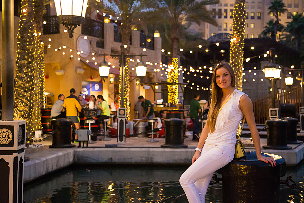 Beautiful girl in white sitting in the bar in the evening time in Dubai, United Arab Emirates (UAE)