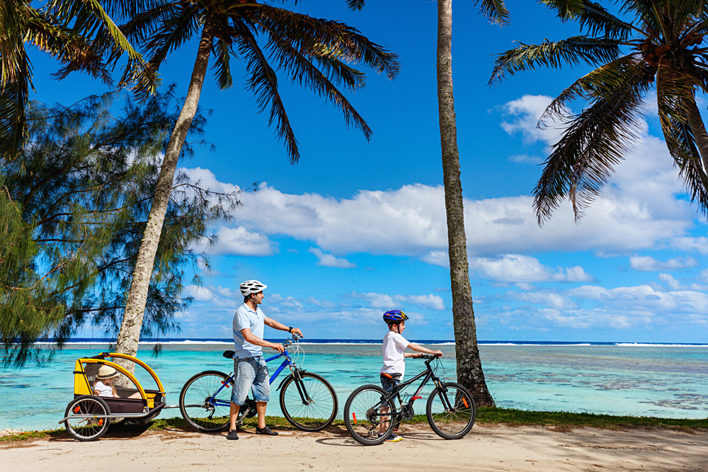 Father and kids biking in Rarotonga, Cook Islands