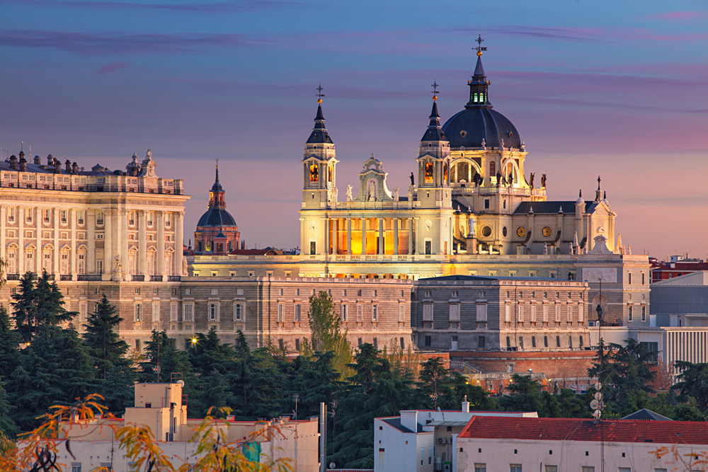 Madrid skyline with Santa Maria la Real de La Almudena Cathedral and the Royal Palace during sunset, Spain