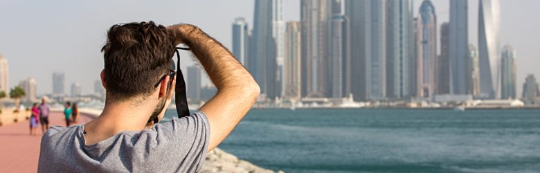 Male Tourist taking photo of the Dubai Marina skyline, United Arab Emirates (UAE)