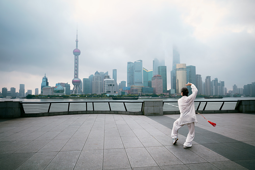 Shanghai Skyline at sunrise with man doing Tai Chi, Shanghai, China