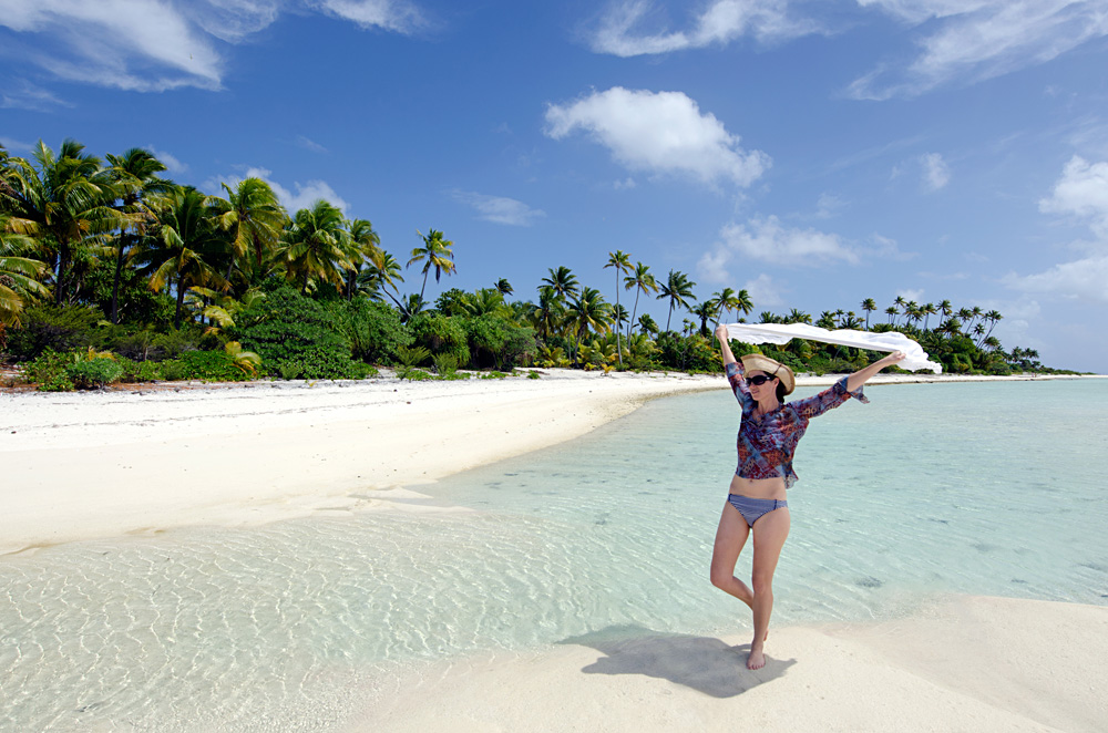 Young woman relaxing on a deserted tropical island in Aitutaki Lagoon, Cook Islands