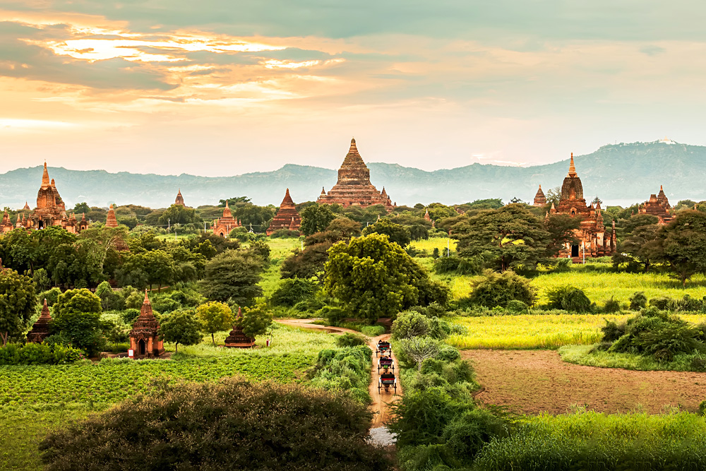 Ancient temples and horse and carriages at sunset in Bagan, Myanmar
