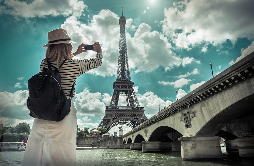 Female tourist photographing the Eiffel Tower in Paris, France