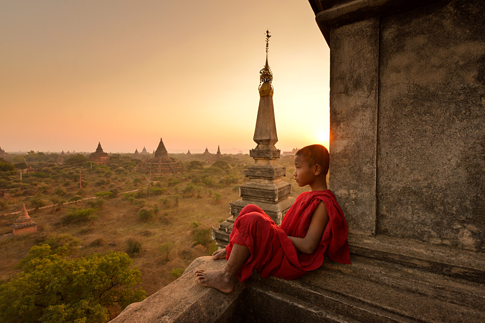 Novice young monk looking out at plains of Bagan during sunrise, Myanmar