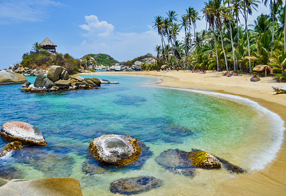 Paradise beach with white sand, palm trees and blue waters of Caribbean Sea in Tayrona National Park in Colombia