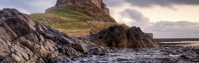 Rugged coastline of Holy Island in Northumberland is protected by Lindisfarne Castle, England, UK (United Kingdom)