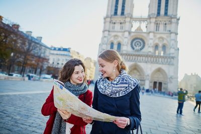 Two young girls walking together with map near Notre-Dame Cathedral, Paris, France