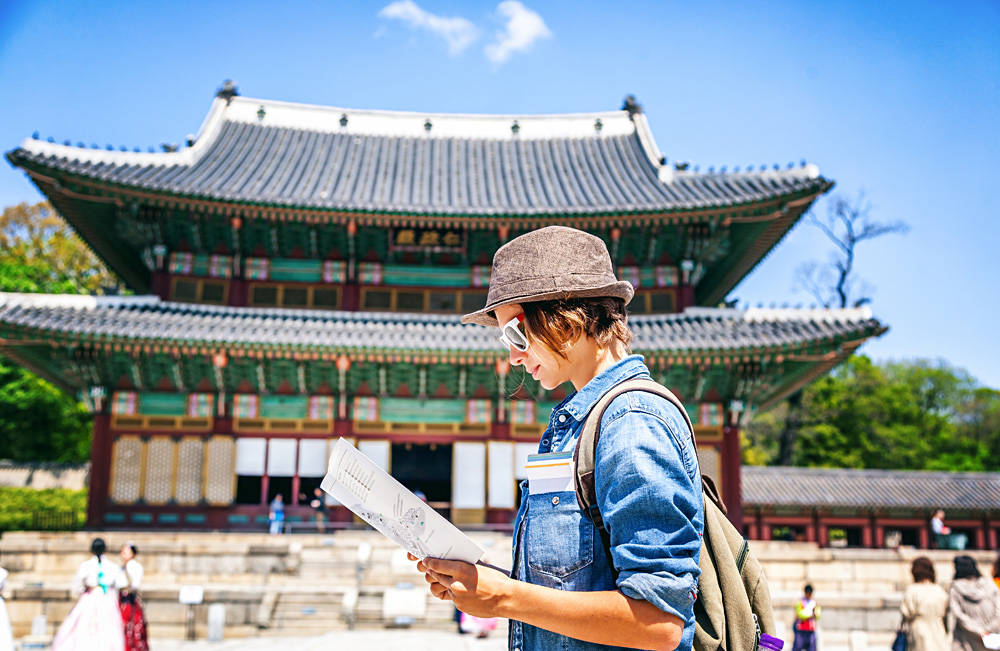Young woman tourist with map in hand with Asian architecture, Seoul, South Korea