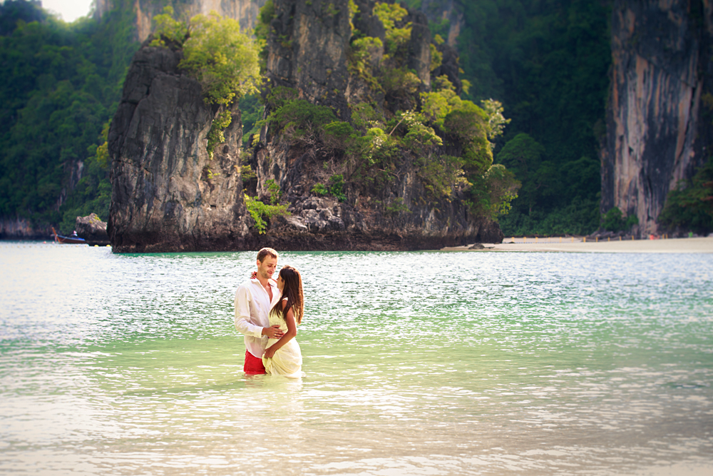 Couple stand in sea water in island bay with karst in background, Thailand