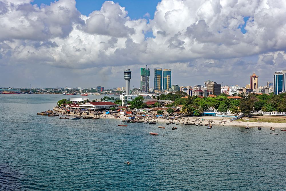 Fisherman boats in front of Kivukoni Fish Market with Port control tower and Skyscrapers in Background, Dar Es Salaam, Tanzania