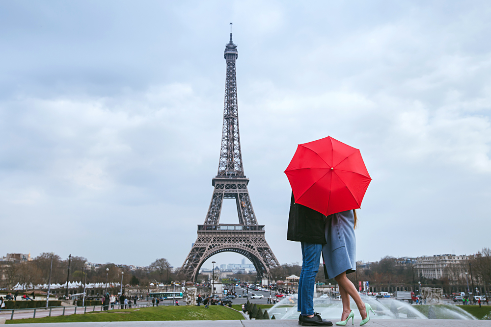 Honeymoon in Paris, Couple kissing behind red umbrella against Eiffel Tower, France