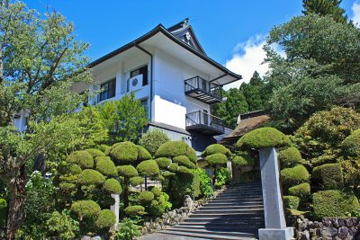 Lush Japanese garden of topiary trees and shrubs lines the entrance to a Buddhist temple in Koyasan, Japan